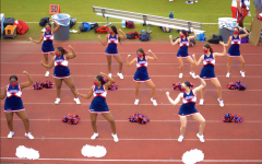 Cheerleaders perform for football fans with masks on.